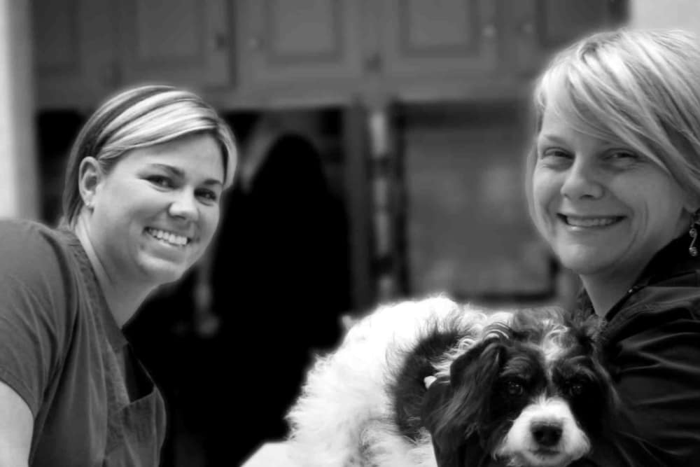 Team members at Oldtown Veterinary Hospital smile and pose with dog