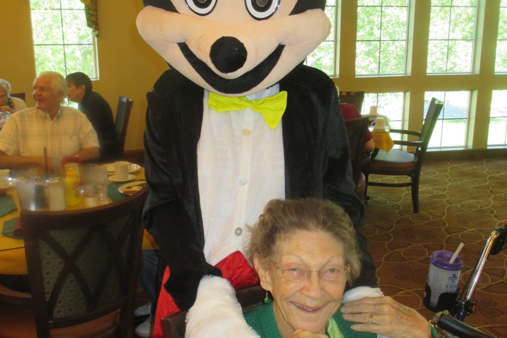 Cartoon mascot interacting with a resident of Eastern Star Masonic Retirement Campus