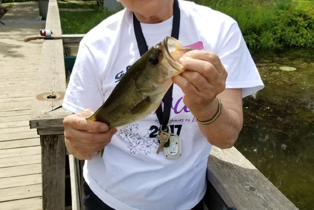 senior resident holding a fish