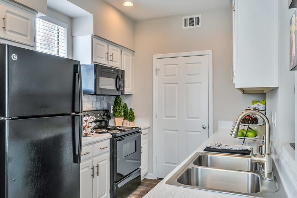 A sleek black refrigerator, oven and microwave at Parc at 980