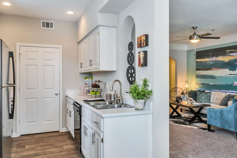 A kitchen with pristine white cabinetry at Parc at 980