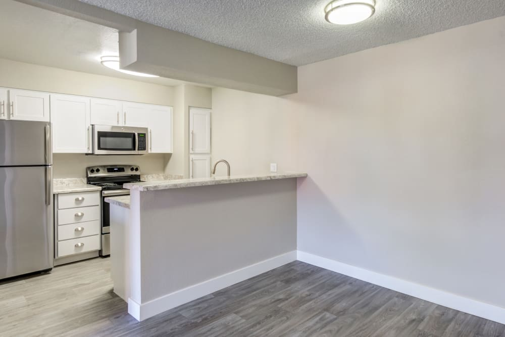 Model kitchen at Elliot's Crossing Apartment Homes showcasing hardwood floors and modern appliances in Tempe, Arizona