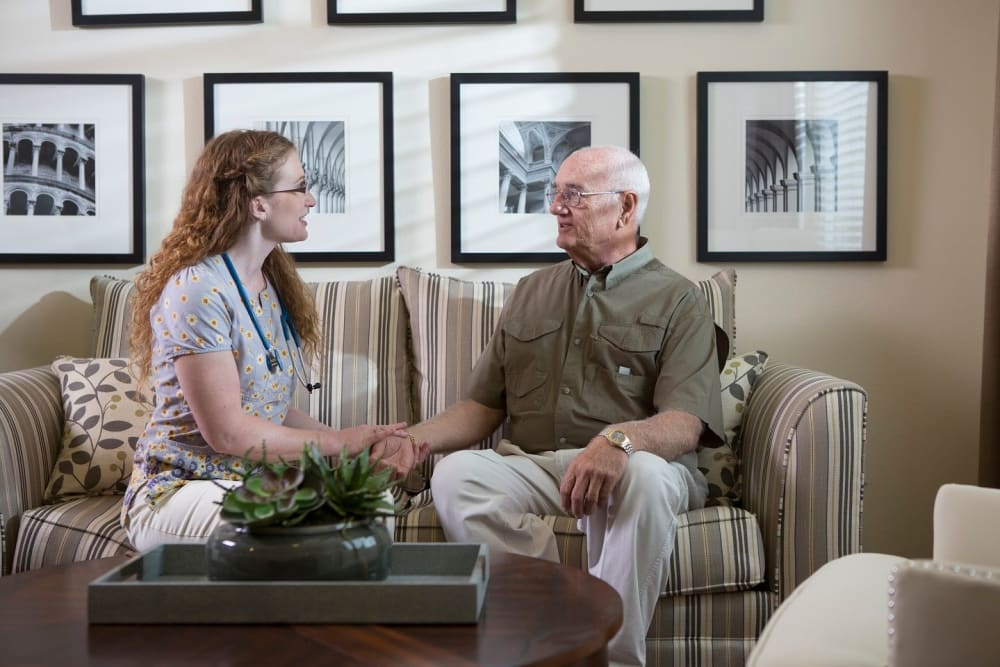 A nurse and resident sitting on a couch Bonita Springs
