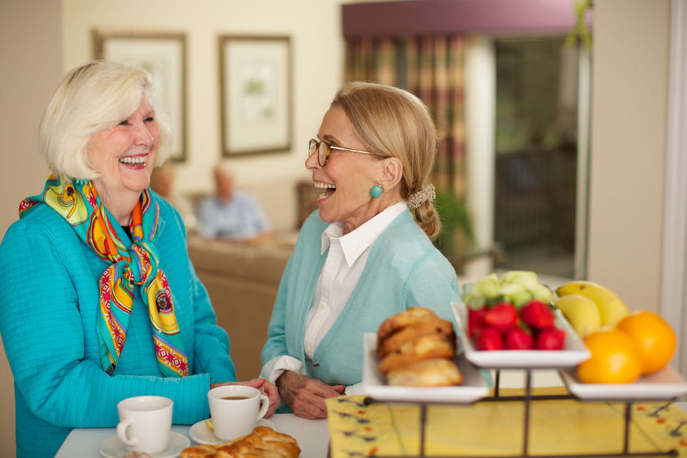 Friends laughing while having espresso and fruit in Bonita Springs