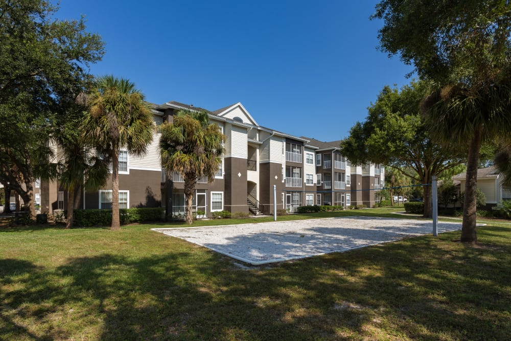 Exterior resident building and sand volleyball court at Tuscany Villas of Brandon Apartment Homes