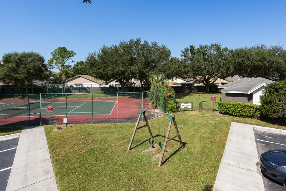 Tennis court and swing set at Tuscany Villas of Brandon Apartment Homes
