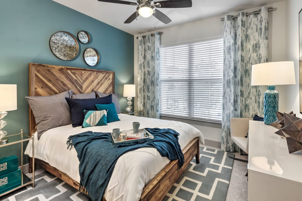 Model bedroom featuring ceiling fan at Juncture in Alpharetta, Georgia