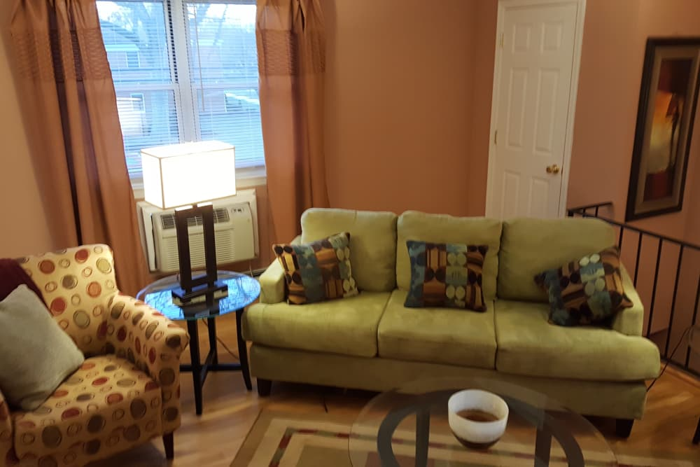 Green couch with patterned pillows at Wingate Apartments