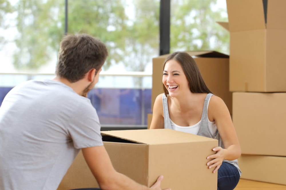 Couple packing boxes to storage them at Dominion Self-Storage
