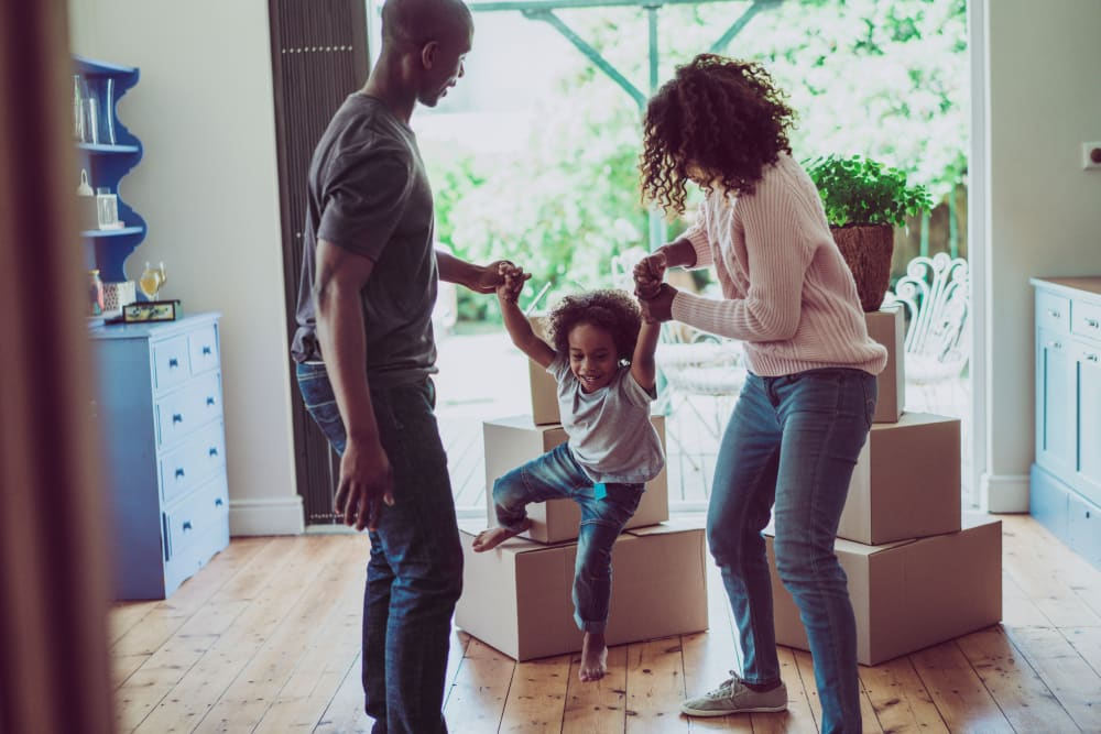 Playful parents holding son's hands in new home in Buckeye, Arizona