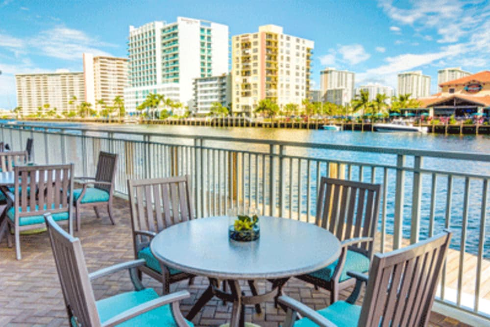 Outdoor seating with a river view at Symphony at the Waterways in Fort Lauderdale, Florida.