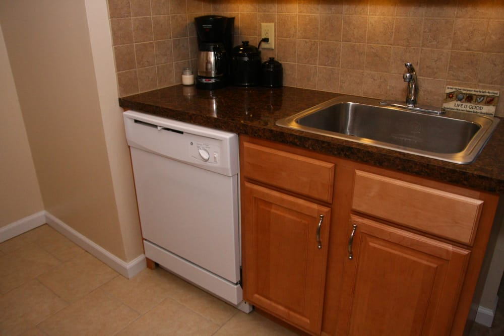 White dishwasher and stainless steel sink at Ocean Harbor Apartments