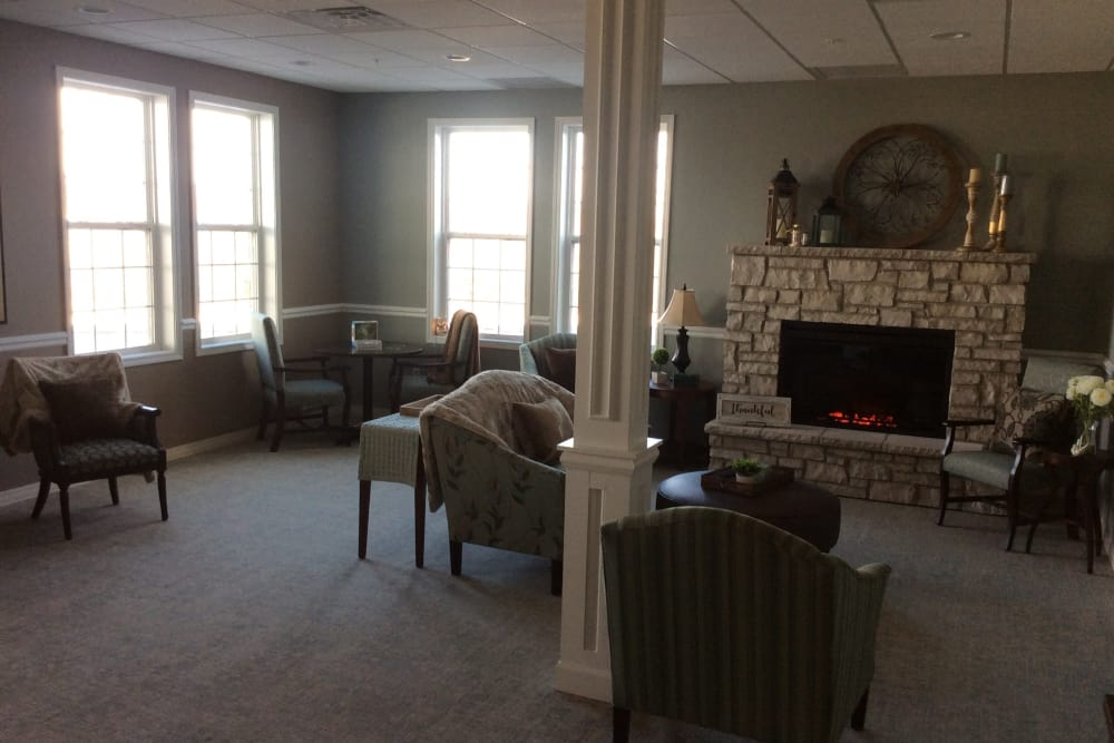 Decorated lounge with a fireplace and seating at Serenity in East Peoria, Illinois