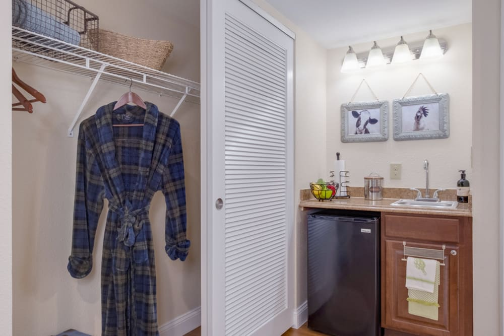 Closet and mini fridge in unit at Grand Villa of Boynton Beach in Florida