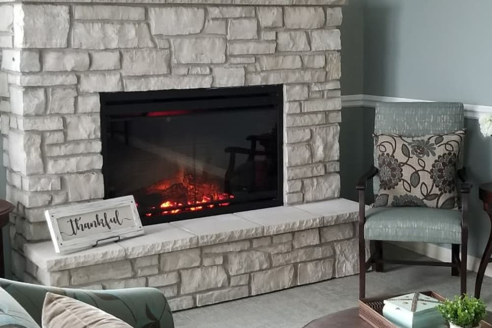 Fireplace with a chair next to it at Serenity in East Peoria, Illinois
