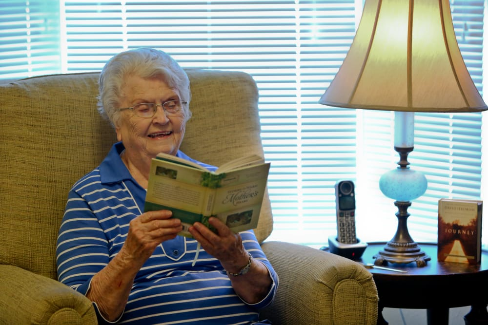 Resident sitting and reading at Azalea Estates of New Iberia