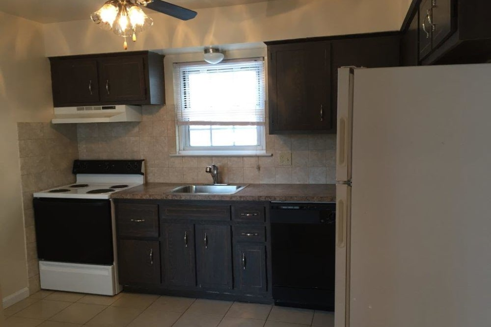 Kitchen with dark cabinets and light-colored appliances at Shenandoah Arms in Spring Lake
