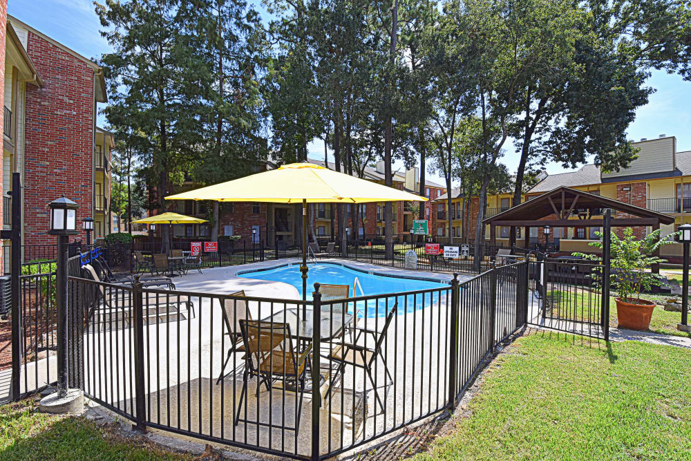 Fenced-in swimming pool at Park at Deerbrook Apartments in Humble, Texas