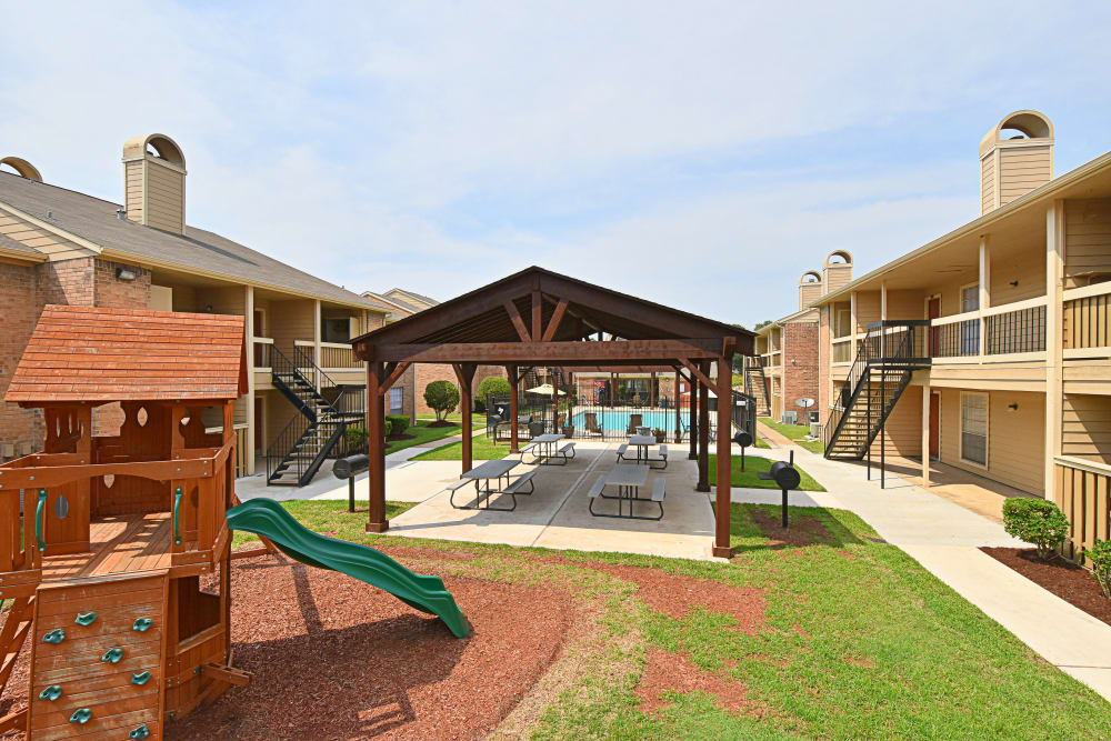 Covered picnic area with playground at Brookmore Hollow Apartments in Rosenberg, Texas