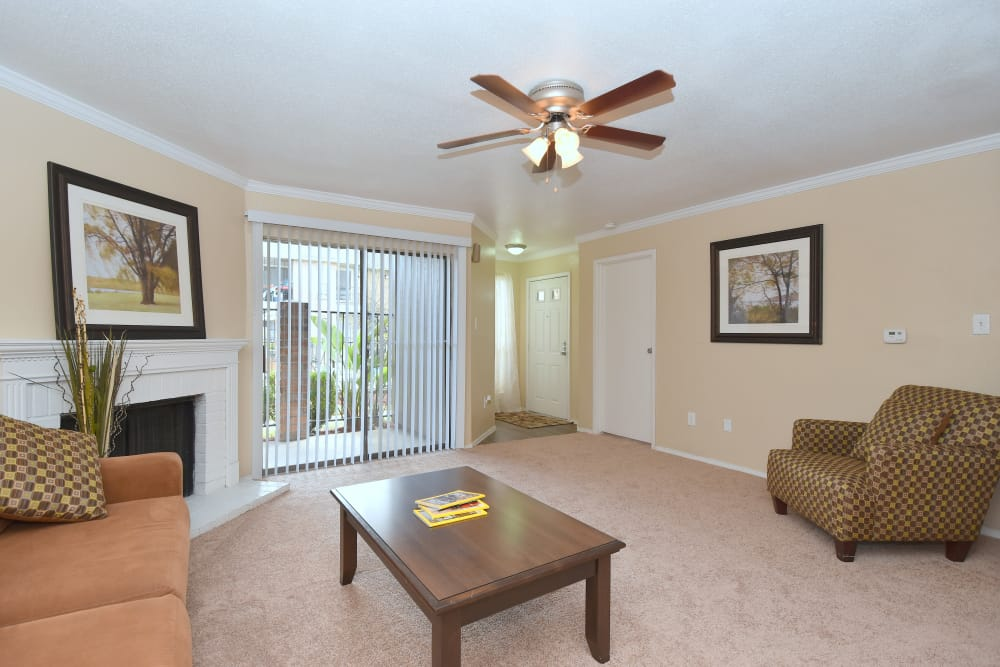 Living room with ceiling fan at Deerbrook Garden Apartments in Humble, Texas