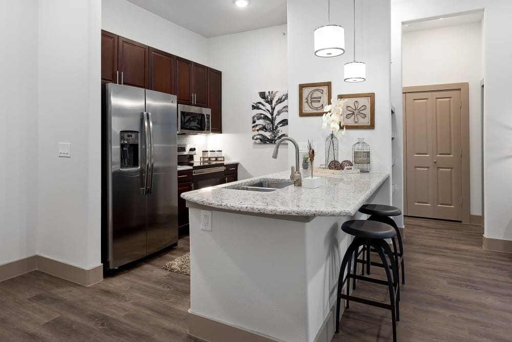 A view of the kitchen with a stainless-steel fridge and breakfast bar at Villas at the Rim in San Antonio, Texas