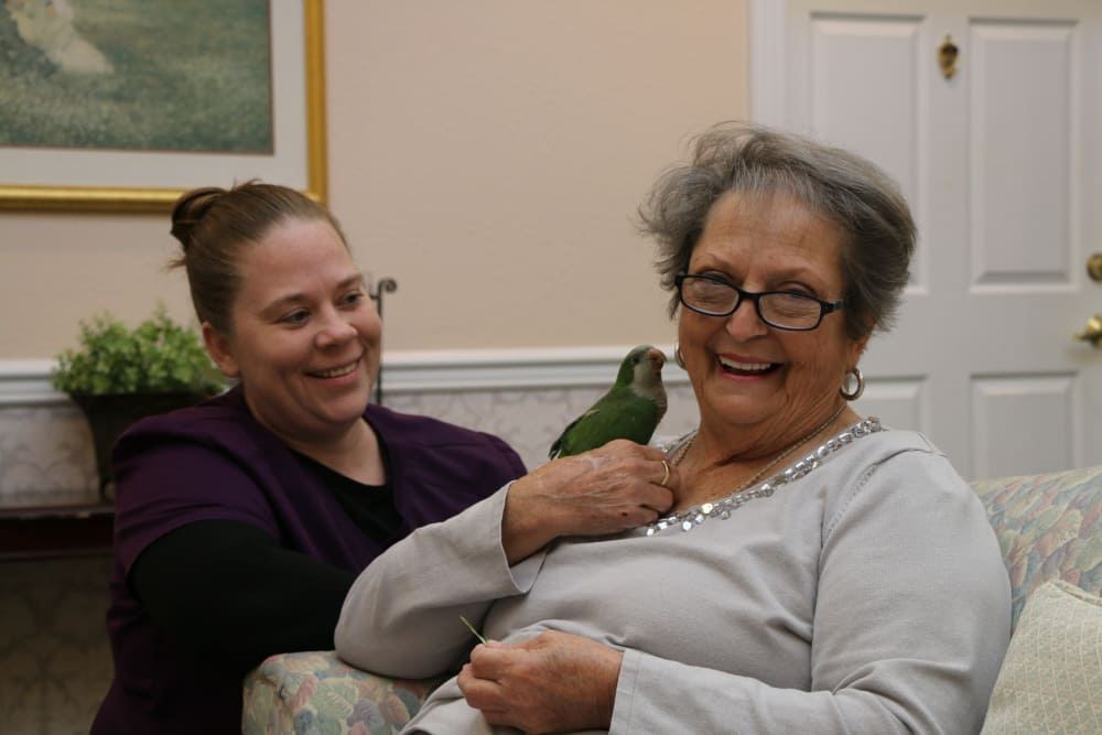 Care provider and resident playing with a bird at Azalea Estates of Gonzales