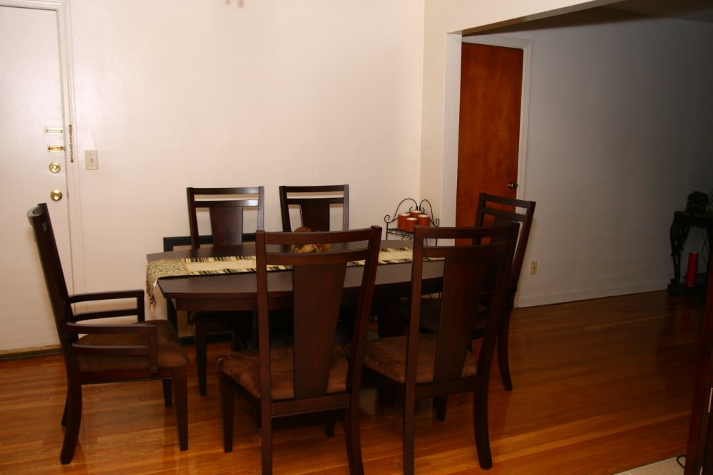 A dining area  with dark wood table and chairs at Royal Court Apartments