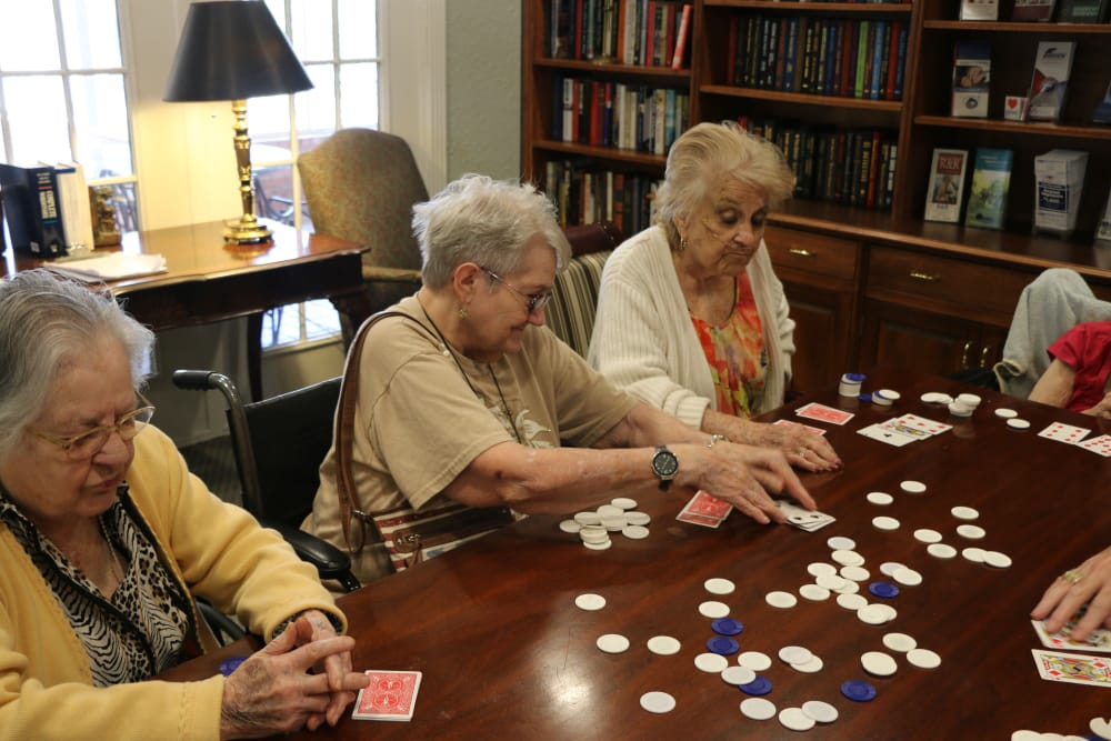 Residents playing poker together in the library at Azalea Estates of Monroe in Monroe, LA