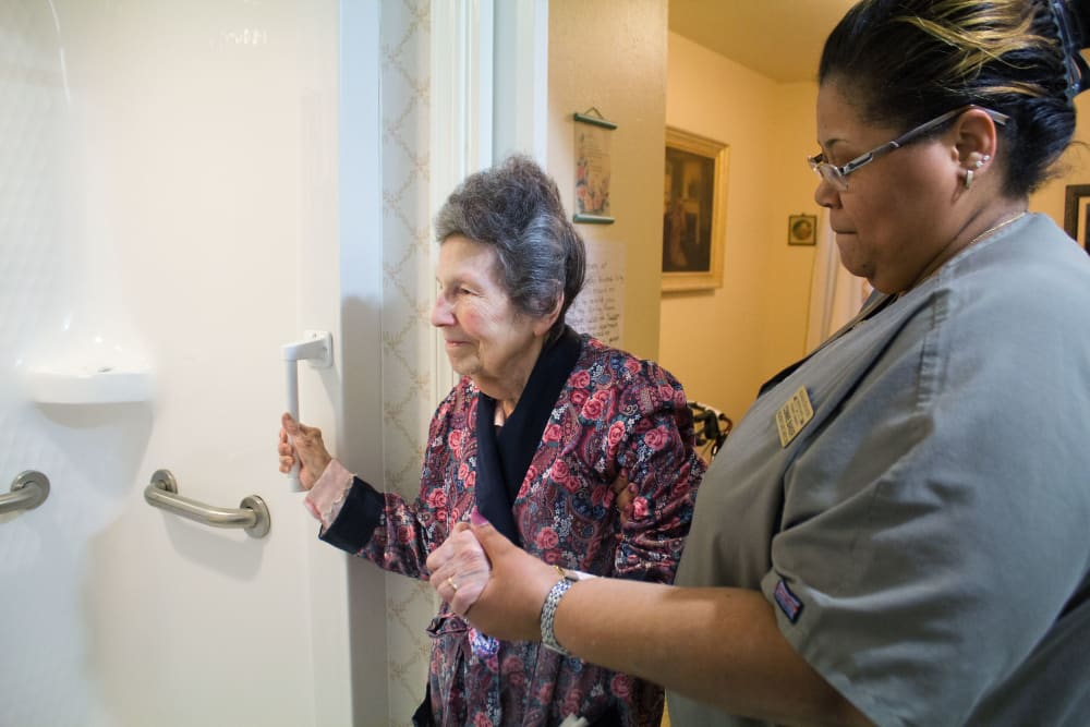 CNA helping a resident into the shower at Azalea Estates of Fayetteville in Fayetteville, Georgia