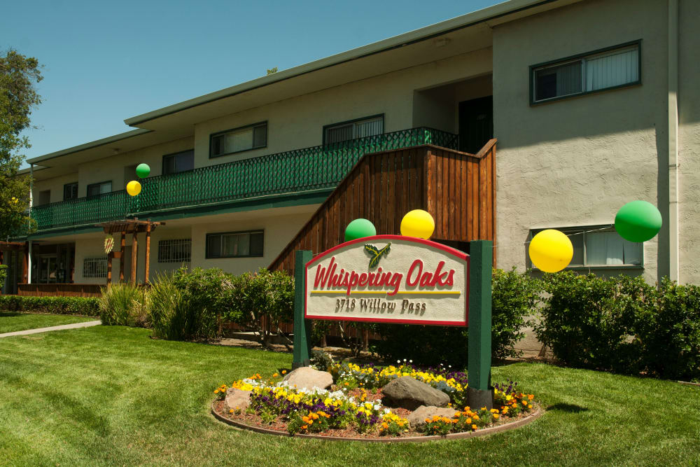 Sign and exterior view of our apartments at Whispering Oaks