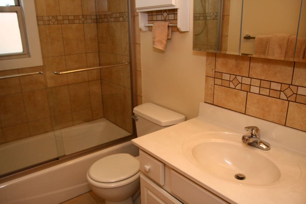 Riverwood Commons bathroom with a white sink, toilet and glass shower door