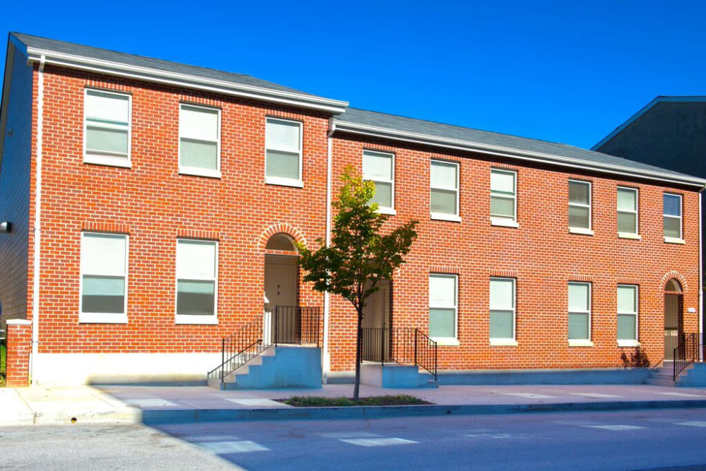 A streetside view of the red brick apartment building at Vintage Gardens in Baltimore, Maryland