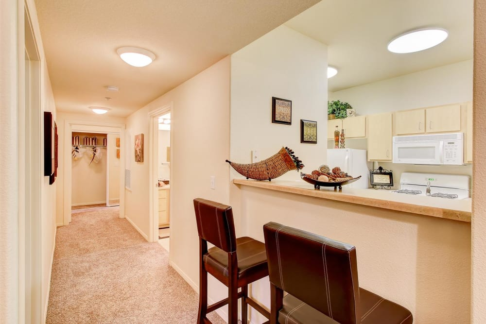 Breakfast bar adjacent to kitchen and hallway view inside model home at Brooks Landing in Modesto, CA