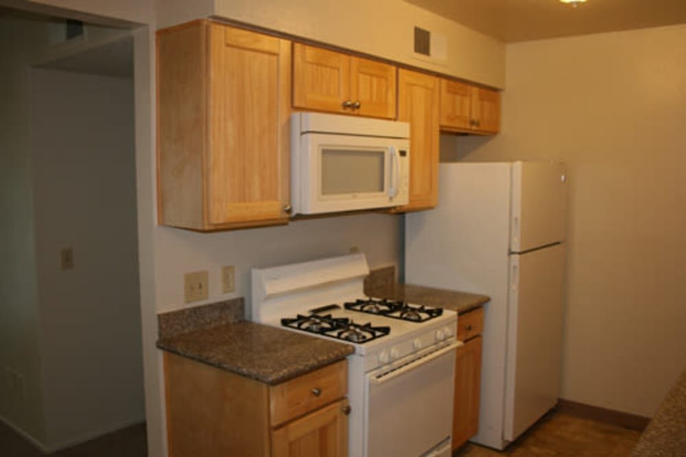 Kitchen with white appliances at apartments in Fresno, California