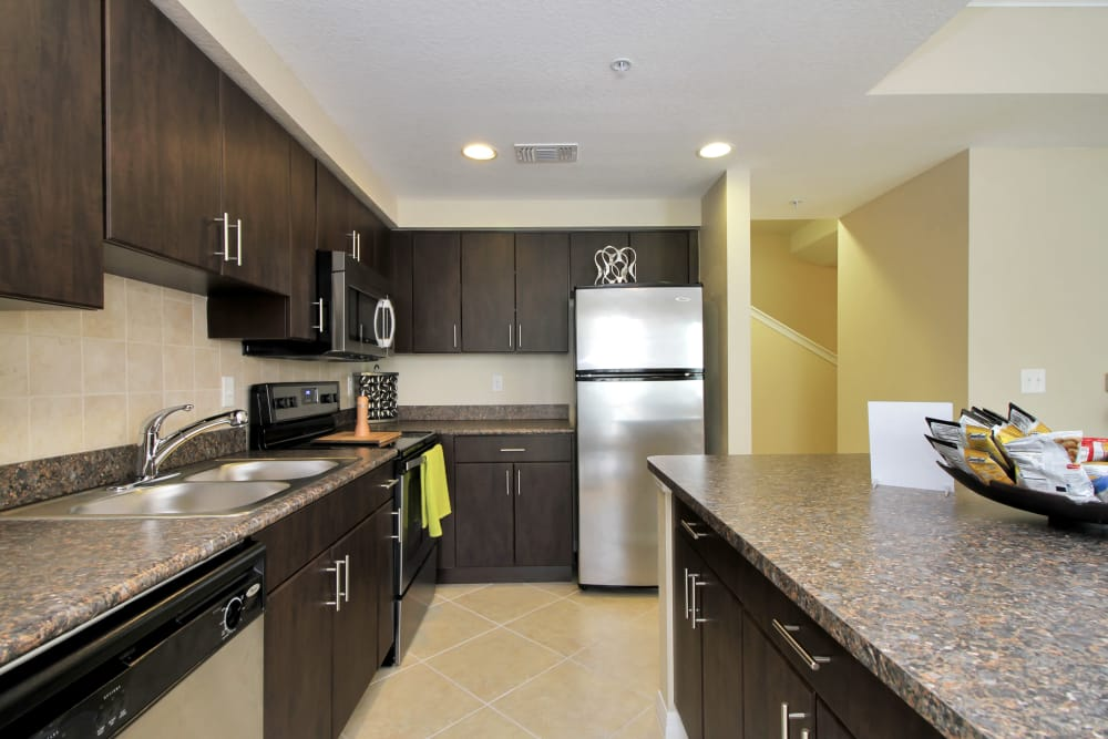 Gorgeous and modern kitchen with dark wood cabinets and stainless appliances in model home at IMT Miramar in Miramar, FL