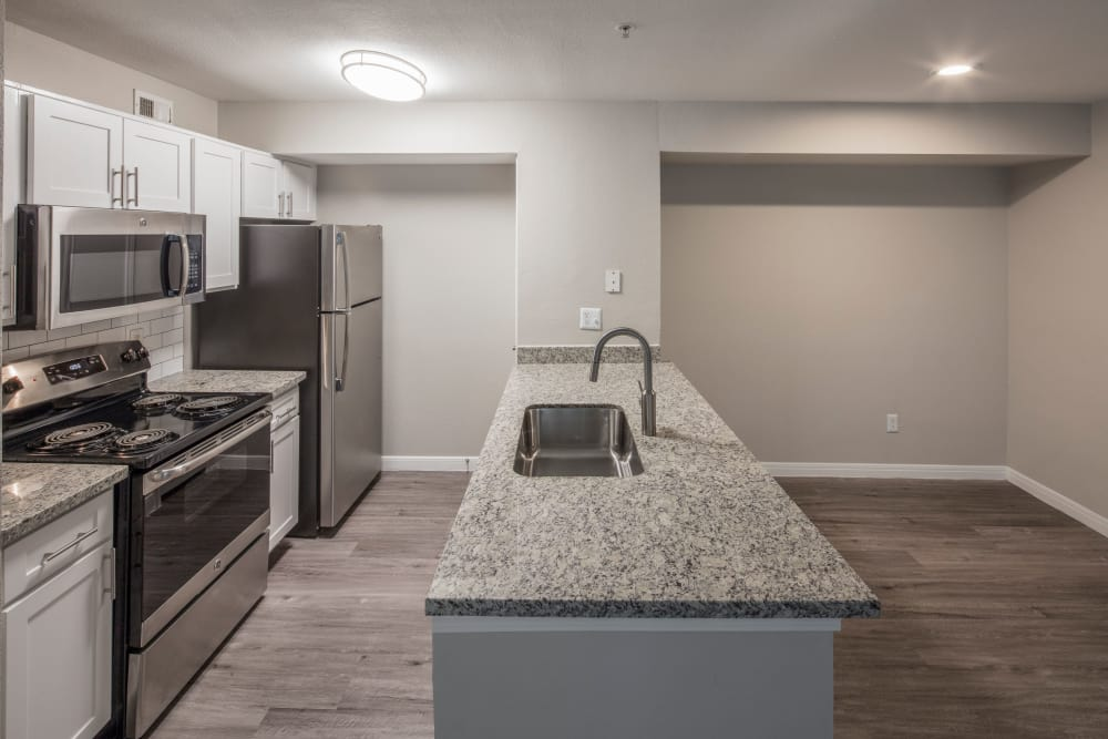 Beautiful floor plan layout showing black appliances, granite countertops, and hardwood-style floors in home at IMT At The Medical Center in Houston, Texas