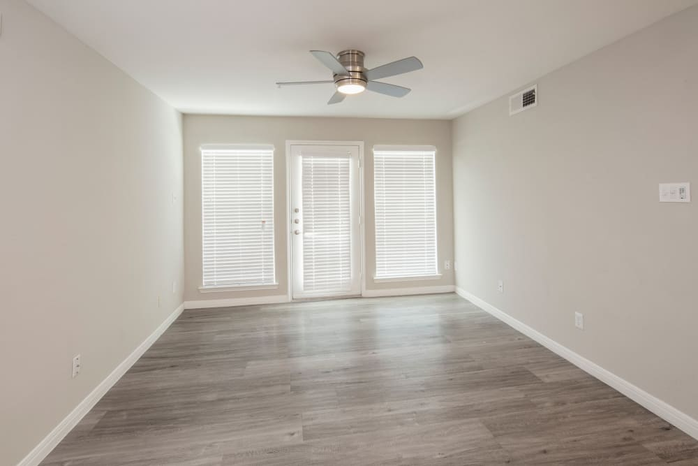 Hardwood-style floors and ceiling fan in empty apartment home at IMT At The Medical Center in Houston, Texas