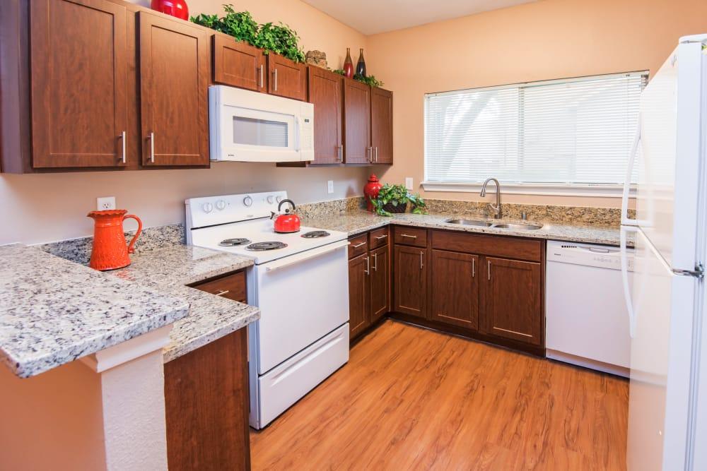 Granite countertops and plank flooring in a kitchen at Villas of Preston Creek Plano