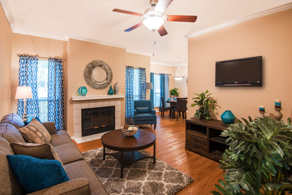 A cozy living room with ceiling fan and fireplace at Villas of Preston Creek in Plano, Texas