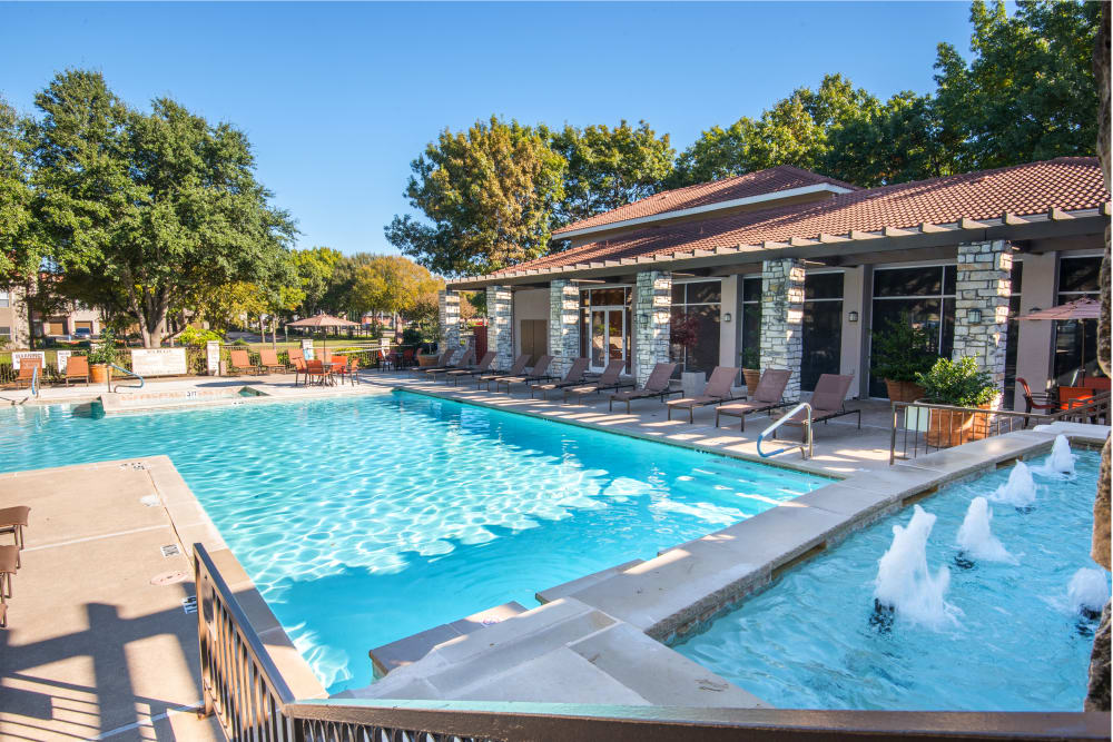 The swimming pool on a sunny day at Villas of Preston Creek in Plano, Texas