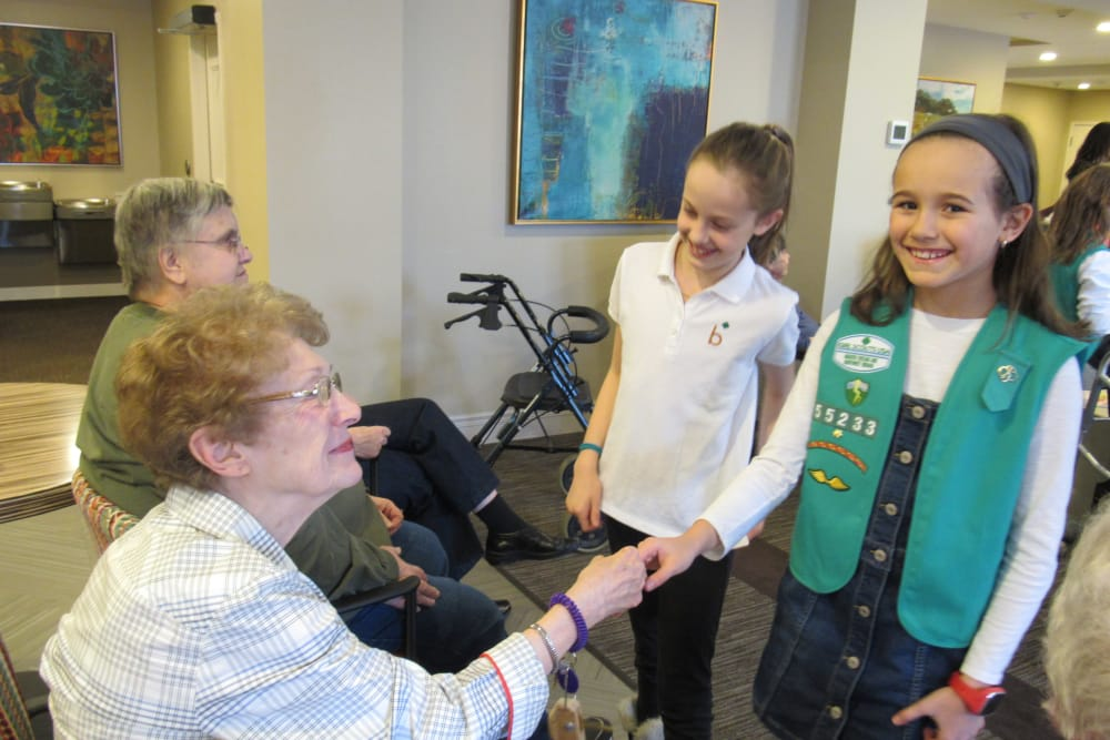 senior residents shaking hand of young girl