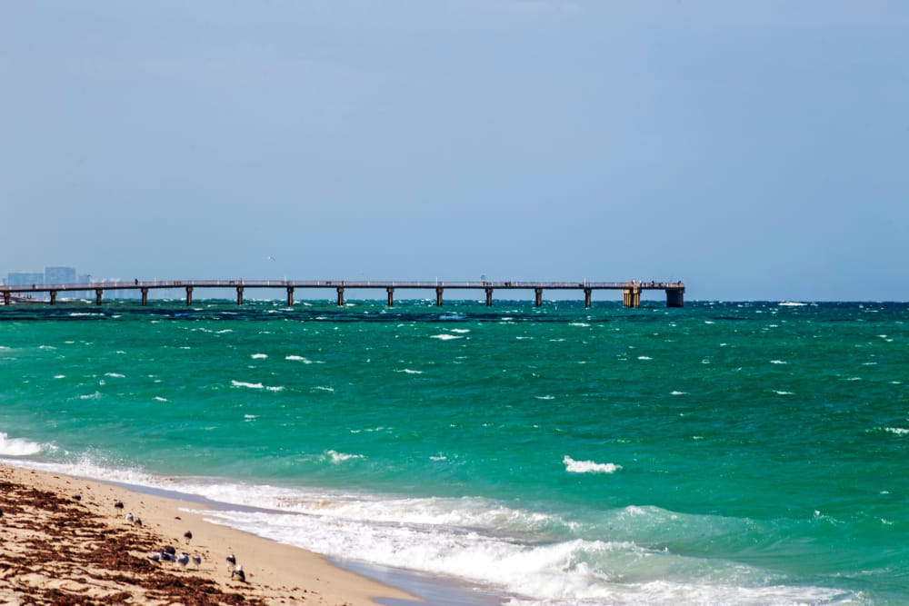 View of the pier stretching out into the ocean from the beach near Aliro Apartments in North Miami, Florida