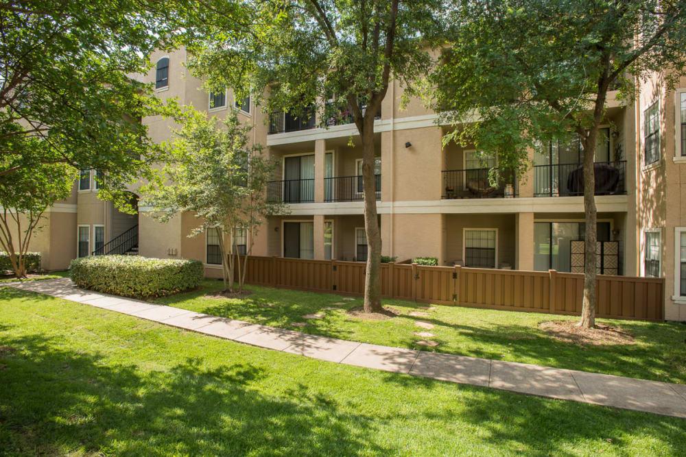 A walkway and fenced backyards at Briargrove at Vail in Dallas, Texas