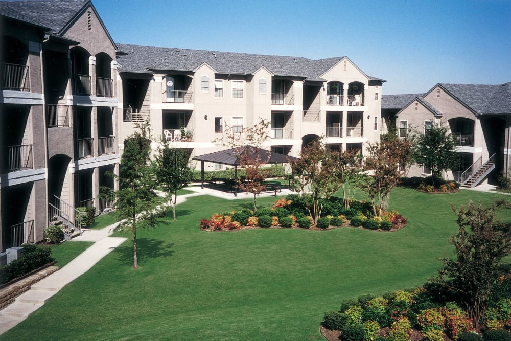 Apartment buildings and a large common lawn at Briargrove at Vail in Dallas, Texas