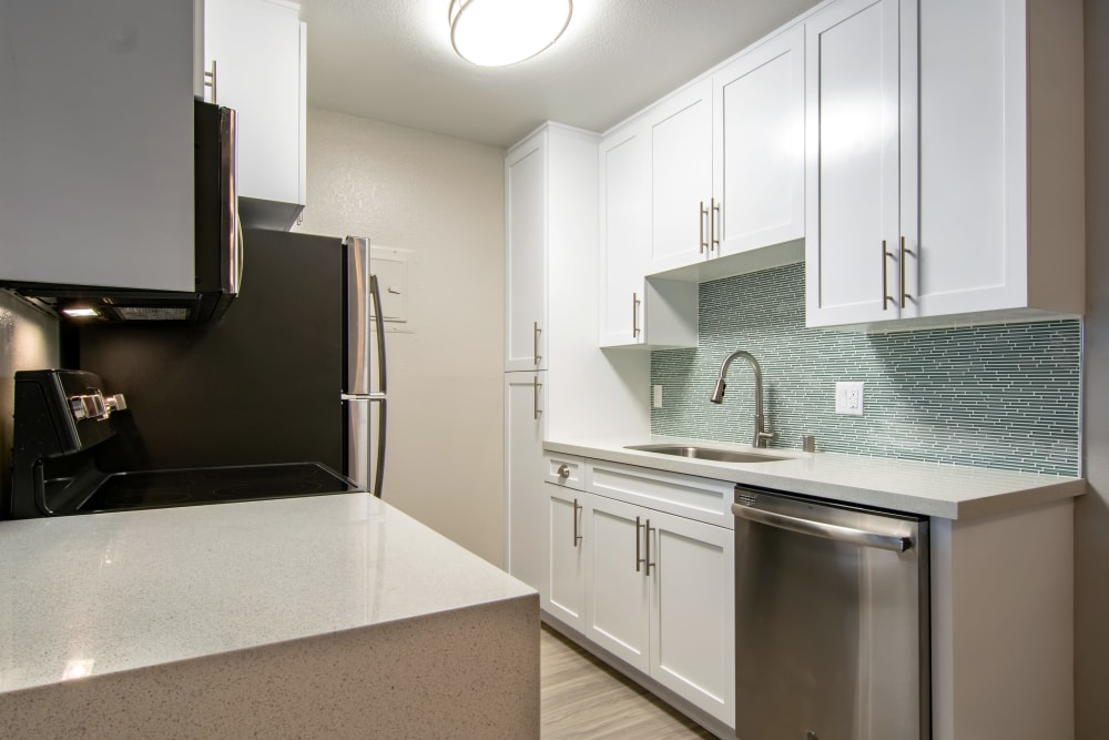 Kitchens with tiled backsplash at Avana La Jolla Apartments in San Diego, CA
