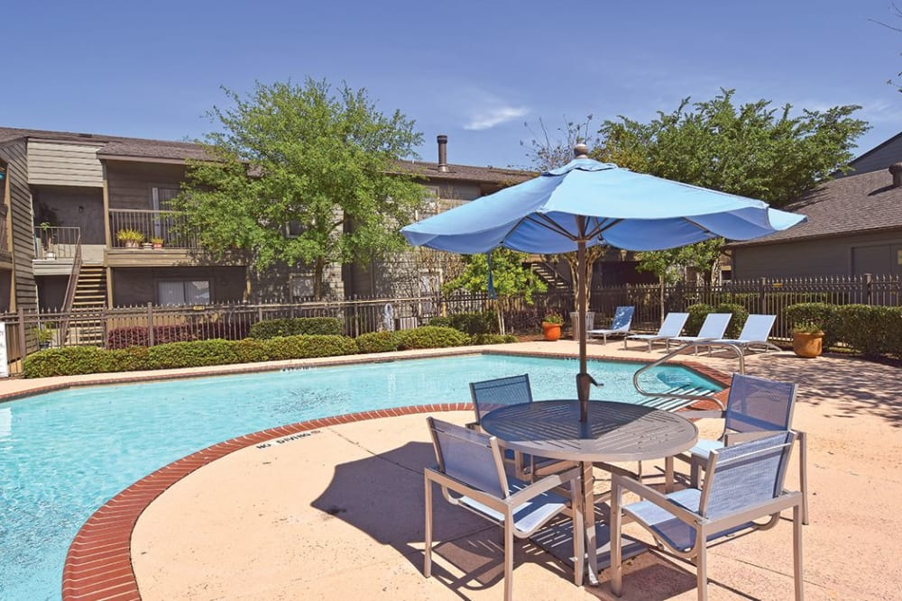 Umbrellas, tables and chairs near swimming pool at The Lodge on El Dorado in Webster, Texas