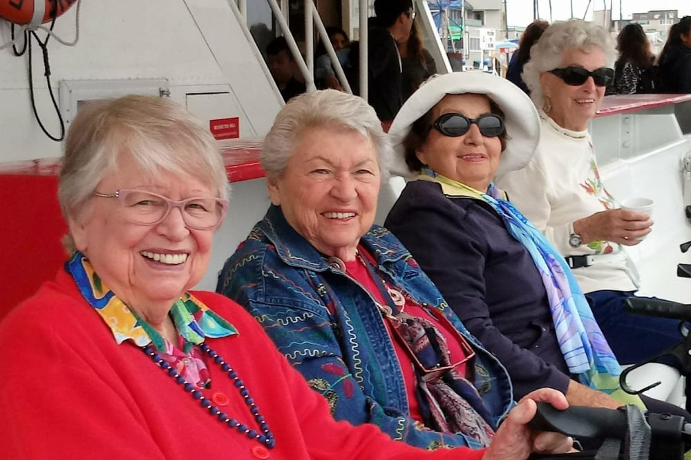 Residents smiling together at Merrill Gardens at Huntington Beach outing