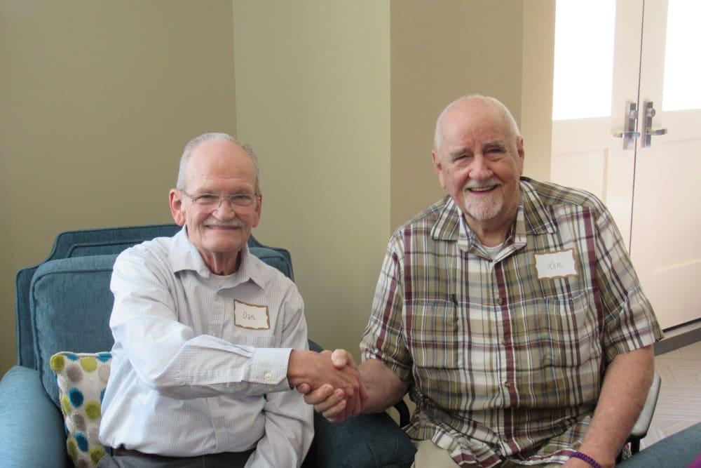 two senior residents shaking hands