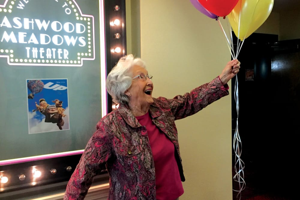 A resident of Hawthorn Senior Living in Vancouver, Washington posing for a picture, holding balloons