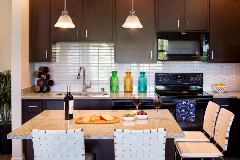 Gourmet kitchen with black appliances and dark wood cabinetry in model home at Kapolei Lofts in Kapolei, HI